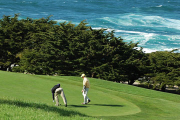 two golfers on the green at an oceanside golf course